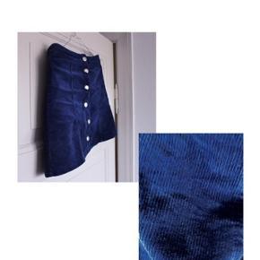 - Retro nederdel  - Fløjls  - Farve: en blanding af petroleums blå og marine blå  - Fra H&M  Pasform:  Sidder perfekt i en str.36/S, men en str. XS kan fint passe den, så er den bare lidt længere og sidder lidt mere lavtaljet.