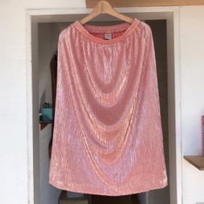Den festligste nederdel i smuk Rosa farve, passer egentlig alle sæsoner.  Størrelsemærke mangler, men den kan fitte alt mellem Medium og XL, da der er elastik i talje og stof.  Bytter ikke.