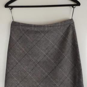 Nederdel med foer. Lynlås bagpå. Længde målt bagpå: 49 cm.  Talje målt indvendigt hele vejen rundt incl. lynlås: 82 cm. 32% uld, 50% polyester, 11% acryl, 5% polyamide.