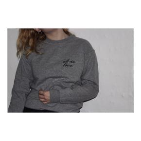 Grå sweater med sort broderet skrift i størrelse small.  Aldrig brugt.