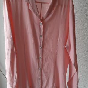 """Fin lyserød skjorte med perlemorsknapper. Kender ikke materialet, men den er mere """"tung"""" end let."""