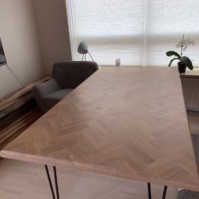 Nyt, lækkert håndlavet sildebens spisebord i eg. Lavet på 21 mm krydsfiner, med egefiner på undersiden. Sortlakerede hairpin ben, som er fræsede op under bordpladen. Sildeben er overlagt på kanter på massive egelister, med 45° fræsning, altså ingen klodsede (skjule) kantlister. Lækkert detalje bord, i den rigtige kvalitet. Behandlet med Faxe Hvidolie.
