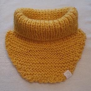Hjemmestrikket halsedisse i 100% norsk superwash uld. Den er kortere bagpå så man ikke skal slås med at den kravler op når man skal have sin jakke på. Farven er varm fyldig bio-æggeblomme gul.