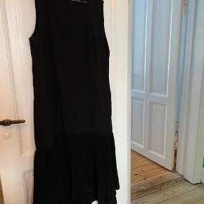 Sort midi kjole fra cos, kun brugt enkelte gange. Har flæse for neden og er uden ærmer
