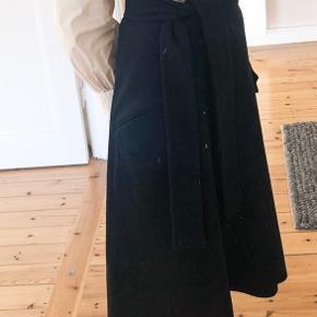 Flot mørkeblå nederdel i det fineste snit, det er slå om med knapper og bælte i siden. Materialet er uld-agtig