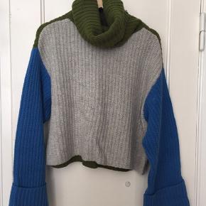 Sej blokfarvet sweater med store ærmer og rullekrave. 95% uld og 5% cashmere. Kun brugt en enkelt gang.