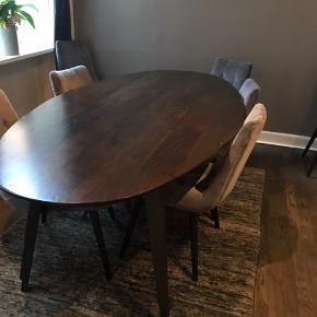 Ovalt spisebord i mørk træ  200X100 cm  Fremstillet af kraftig, mørkt og finslebet mangotræ og med bordben i sort jern med en flot, glat overflade .  Står på et kontor og er kun et halvt år gammel.   Afhent selv (står i indre K, 1114).