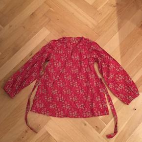 Så sød skjortebluse i det lækreste Liberty bomuld. Den har en lille knaplukning ved halsen og et fint bånd i taljen, der kan bindes foran eller bagpå.Kun brugt en enkelt gang.  Tjek min profil for andet tøj syet i lækkert Liberty stof