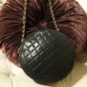 Chanel vintage taske i kraftig skind, med guld hw, og serienr i. Kan også bruges som crossbody. Helheden på tasken er fin, bortset fra omkring lynlåsen, hvor der er brugsspor. (ses på det sidste billede). Det samme gælder taskens indre. Den er godt brugt, men fejler intet til brug.  Tasken har to sider så tasken kan vendes som man ønsker.