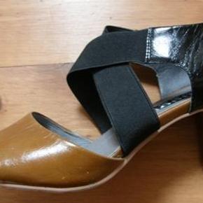 """Brand: Phigo tre-farvede Varetype: Sandaler med elastik Farve: sort tan creme Oprindelig købspris: 899 kr. Kvittering haves. Prisen angivet er inklusiv forsendelse.  Elegante og meget velsiddende sko fra Phigo. Nærmest en sandal forrest og en sko/pump bagerst. Har ikke fået brugt dem endnu - de er ægte """"Aldrig Brugt"""" (-;  Kan bruges som sandal eller festsko, med eller uden strømper. Med sorte strømper """"snyder"""" man sig til at se ud som om man kan gå med slippersagtige sandaler, som, som ikke sidder fast om foden.  Byttede dem fra str. 39 til 40 for at kunne have min korte, men brede fod i dem. Synes desværre stadig, at de er for stramme over forfod og nu er byttetiden for længst overskredet. Det skønne ved dem er ellers, at elastikken får dem til at sidde godt fast i forhold til andre sandaler.  De kostede 900 kr. Og jeg betalte porto to gange for dem...!  De kan blive dine for det halve: 450 kr. alt inkl. NU SAT NED TIL 400 ALT INKL.  Og så sender jeg dem i den originale kasse som forsikret DAO-pakke uden omdeling."""