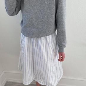 Nederdel med bred elastik i talje og lommer i siderne.  Nederdelen har ingen pletter og er i god stand.