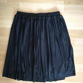 Sort, lidt plisseret nederdel med stræk i taljen.
