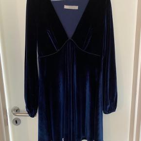 Fin og elegant velour kjole i marine blå. Den er så fin og super lækker at have på. Den er med elastik i ærmerne og et flot snit på brystet. Den er i str. 36