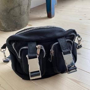 Núnoo Ellie Scuba taske i Sort med sølv detaljer. Ekstra lang justerbar og aftagelig rem medfølger. OBS - der er et lille hul i toppen af tasken, men ellers fejler tasken intet.  Mål: L: 24 cm x H: 16 cm x D: 10 cm