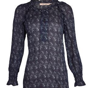 Smuk bluse i viskose. Let gennemsigtig. Med knapper foran på brystet, bredt elastikstykke ved ærmerne og små flæser ved skulderne. Brugt et par gange. Alm str S/36