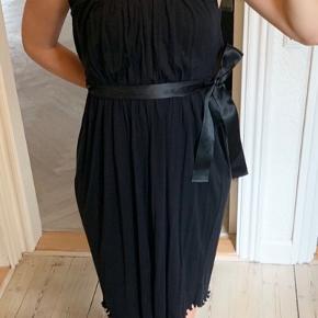 Kjolen er lavet af tyndt strik uldblanding, som er plisseret. Båndet er satin.