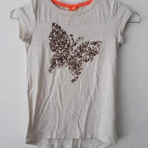 Varetype: Skøn t-shirt med sommerfugl palietter tryk og guldtråde Størrelse: 7år Farve: Creme og guld Oprindelig købspris: 199 kr.