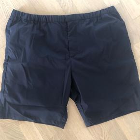 """Flotte lette shorts i """"badeshorts"""" kvalitet, men med lynlås og knaplukning for at give dem et """"hverdags"""" look. Elastik i linningen.  Farve: Ensfarvet mørkeblå  Livvidde: 94-110cm. Benlængde: 21cm. (Innersømmen)"""