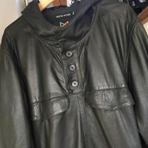 Anorak med hætte i sort læder fra Wood Wood. Blød og lækker. Stort set ikke brugt. Sender gerne! Kom gerne med bud.