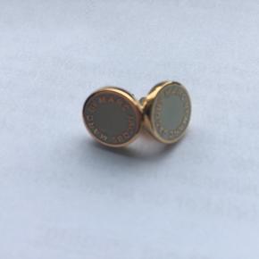 Fine øreringe fra Marc Jacobs. Guld med hvis/beige plade.