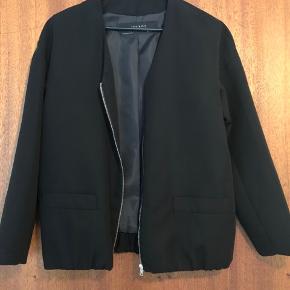 Med elastik kant i bunden - minder om en blanding mellem blazer og bomber jakke.  Kan måske også passes af en small.