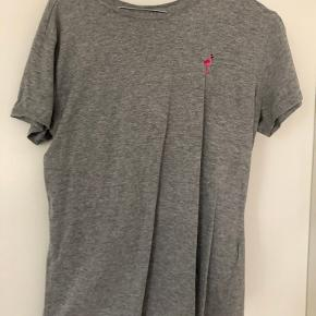 T-shirt fra JDY med pink flamingo v/venstre bryst. Str. M Farve: Gråmeleret  Den er kun brugt 2 gange.