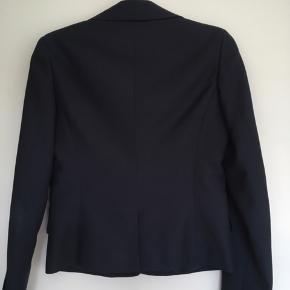 Flot jakke med for og tre knapper. Inderlomme med knap og snydelommer fortil. Meget mørkeblå.
