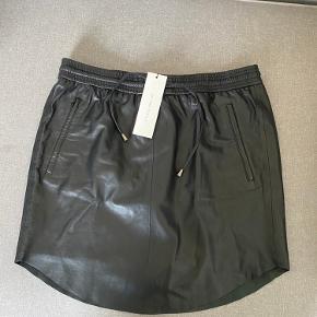 Sort skind nederdel med snøre i livet og lommer i siden. Lækkert handskeblødt skind. Helt ny.