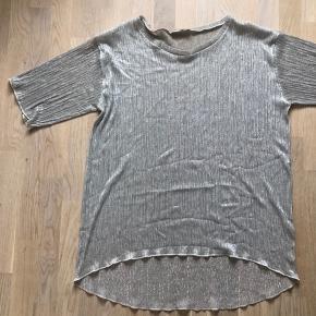 Oversized t-shirt med glimmerdetaljer i stoffet. Super sød og kan styles på flere måder. Mærket er ArGande og den er købt i tøjbutik i udlandet.