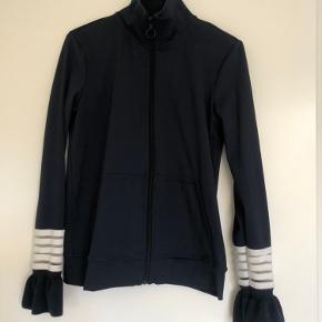 Sporty cardigan/trøje med lynlås op i halsen Lommer foran og flæser på ærmerne   Fin under en vest