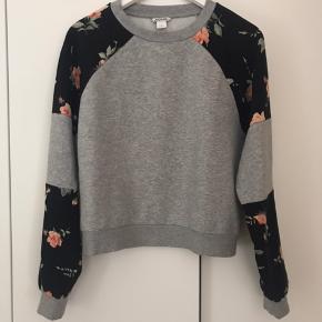 Lysegrå sweatshirt fra monki med blomsterprint på ærmerne.