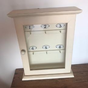 Det fineste lille nøgleskab, med 6 kroge. Kan også bruges til smykker eller andet.  Er i en cream/beige farve. Perfekt til sommerhuset, entréen eller kontoret.   H. 33 cm B. 25,5 cm D. 8 cm