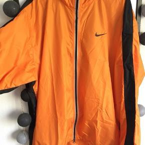 Træningsjakke fra Nike str. L (herre). Let oversize til dame L, hvilket blot giver et retro look. Der er ventilation på ryggen (se billede tre).   Kan sendes med DAO på modtagers regning.
