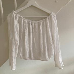 Hvid off shoulder bluse fra Gina Tricot.  Der er elastik kant i bunden