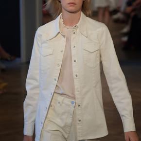Skøn Merinda skjorte fra Baum und Pferdgarten.   Skjorten har et denim-lignende udtryk med to brystlommer og trykknappe-lukning. Derudover er looket klassisk og enkelt.   En tidsløs og klassiske skjorte der nemt kan styles op og ned efter anledning.  Brugt 1 gang.     Materiale: 90% bomuld 7% polyester 3% elasthan