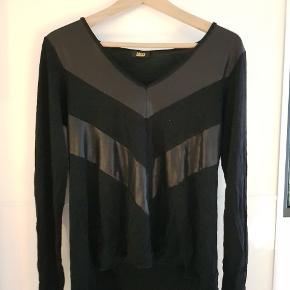 Fin sort trøje med fine læder look detaljer. Har lidt tyngde så den falder rigtig fint. Lugter lidt af kælder efter opbevaring, men det går væk i vask. Der står Moss i trøjen men ikke Moss Copenhagen, så det er nok ikke det samme😊