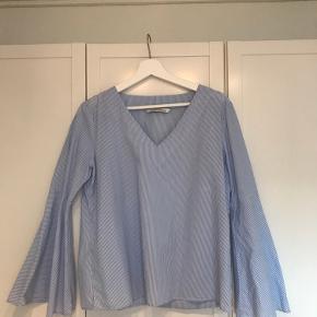 Bluse med hvide/lyseblå striber  Bred v-udskæring  Store ærmer  Brugt få gange   Mængderabat