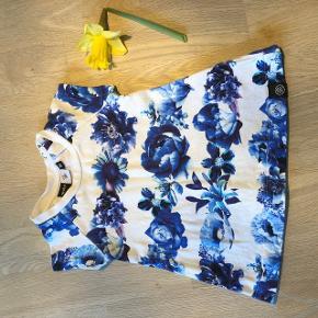 Sød Molo kjole i hvid med blå blomster. To trykknapper bag på kjolen. Størrelse 62/68. Fra røgfrit- og dyrefrit hjem, og vasket uden brug af parfume. Vasket på skåneprogram, og fremstår derfor som ny.