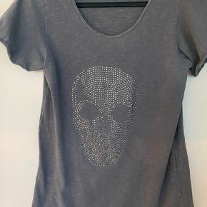 Sej T-shirt med similisten og rå kanter. Er brugt meget lidt, men mangler en enkelt sten. Farven er grå/blå.
