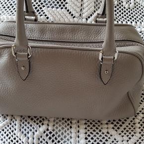 Flot håndtaske i bowling racing i lysegrå skind Mener bare modellen hed handbag  Længde 34 cm Højde 18 cm.  Uden pletter indeni en smule brugsspor på hjørnerne i bunden af tasken.