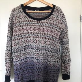 En hyggelig, strikket sweater i norsk-inspireret mønster med fade-effekt. Sweateren er af god kvalitet og fejler ingenting, selvom den er brugt.