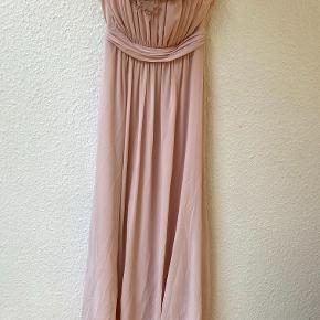 Rosa, lang galla-kjole uden ærmer, med påsyede blomsterdetaljer ved brystet og lukning i ryggen ved lynlås. Kjolen er brugt én gang.