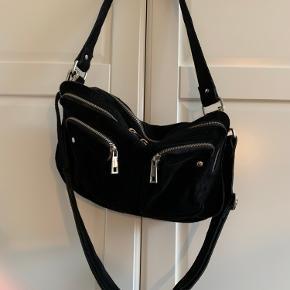 Nunoo taske i sort ruskind. Fremstår som ny, brugt få gange. Mål: L: 34cm, H: 19cm, B: 10cm Køber betaler fragt.