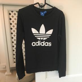 Sort Adidas trefoil sweatshirt i str. XS/UK 6. Har været brugt en del, men er uden særligt synlige tegn på slid.