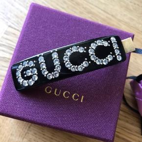 Overvejer at sælge mit smukke hårspænde fra Gucci. Det er købt hos Gucci i Berlin i 2019 af min mand. Måler 8 cm.  Der medfølger smuk pose til spændet og æske.  Sælger ikke til underbud.  Nypris 2600kr  Sælges til højst bydene og ikke under 2000 kr plus Porto.