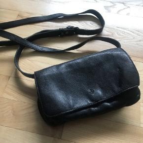 Lille, sort lædertaske med skrårem, nypris 799,- Fra Adax, 22 x 14 cm. Opdelt i to åbne rum, samt to mindre rum med lynlås. Hele tasken lukker med en magnet-knap, og remmen kan tages af, så tasken i stedet fungerer som clutch.