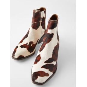 Cowboy-ankelstøvler i læder (gedeskind og skind med kohår) med hæl. Kombinerede farver.  Elastiske sidestropper.  Cowboyhæle med træeffekt. Firkantet snude. Hælhøjde: 4,2 cm.