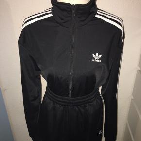 Sort klassisk 3 stripe træningssæt fra Adidas. Bukserne er en large men med elastik og snørre og trøjen er en medium. Hvide striber.