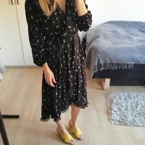 Sød slå om kjole med små blomster og binde bånd. Har en lille sort flæse kant.