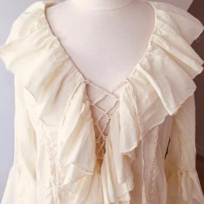 Smuk vintage skjorte tunika/kjole fra Noa Noa.  Smukke detaljer med flæser, bindebånd og broderi.  Har en varm limegul farve - ikke hvid og ikke rigtig gul.  Er lidt for stor til mig desværre.